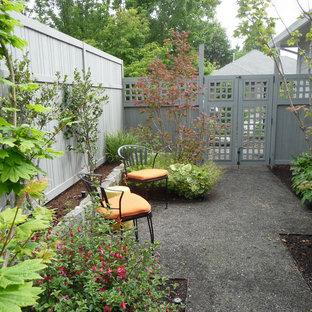 Inspiration för en mellanstor eklektisk trädgård i skuggan längs med huset på våren, med en trädgårdsgång och marksten i betong