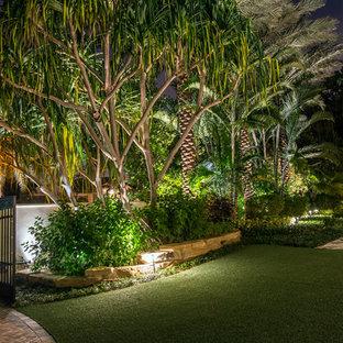 Esempio di un ampio vialetto d'ingresso tropicale esposto in pieno sole davanti casa in estate con fontane e pavimentazioni in cemento