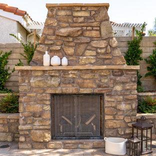 Geräumiger Mediterraner Garten hinter dem Haus mit Kamin, direkter Sonneneinstrahlung und Natursteinplatten in Los Angeles