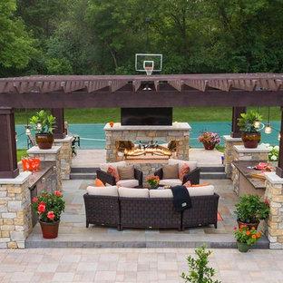 Geräumiger, Halbschattiger Garten im Sommer, hinter dem Haus mit Kamin und Natursteinplatten in Minneapolis