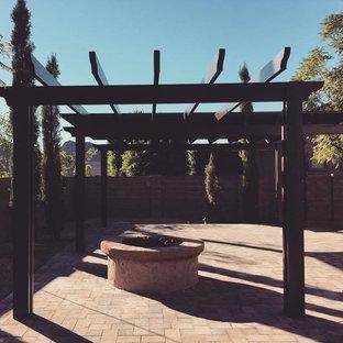 フェニックスの広い、夏のラスティックスタイルのおしゃれな庭 (ファイヤーピット、日陰、天然石敷き) の写真