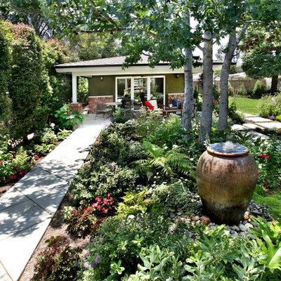 Inspiration for a large traditional partial sun backyard concrete paver landscaping in Orange County.