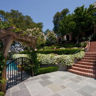 Imagen de jardín clásico, en ladera, con adoquines de ladrillo