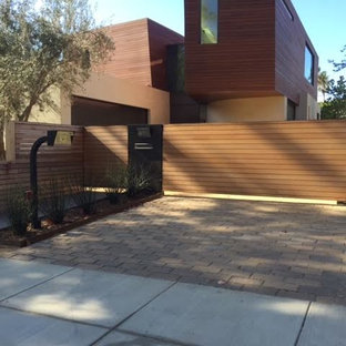 This is an example of a large modern shade front yard brick driveway in Los Angeles.