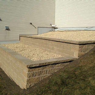 Photo of a mid-sized partial sun hillside concrete paver retaining wall landscape in Minneapolis for summer.