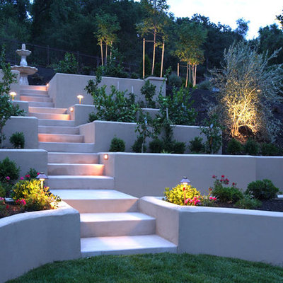 This is an example of a mid-sized contemporary partial sun backyard concrete paver retaining wall landscape in Orange County.