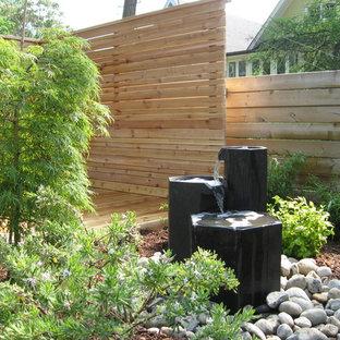 Exempel på en modern trädgård, med en fontän och trädäck