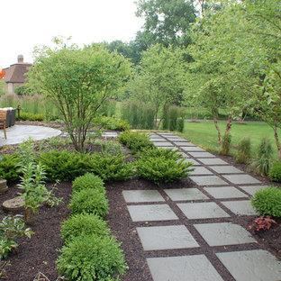 Aménagement d'un grand jardin à la française arrière contemporain au printemps avec une entrée ou une allée de jardin, une exposition ensoleillée et des pavés en pierre naturelle.