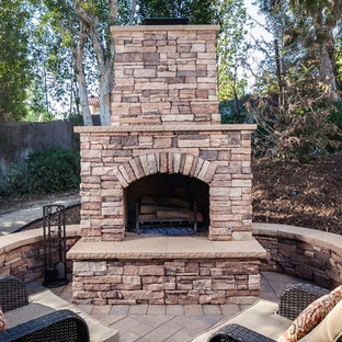 Inspiration for a large rustic backyard stone landscaping in Orange County with a fireplace.