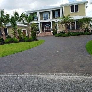 Ispirazione per un grande vialetto d'ingresso tropicale davanti casa con pavimentazioni in mattoni