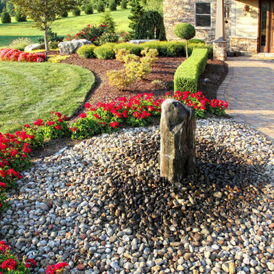 Photo of a traditional full sun front yard river rock water fountain landscape in Other.