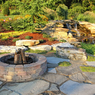 Elegant stone patio photo in Other with a fire pit