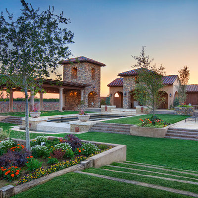 Inspiration for a huge mediterranean full sun backyard stone water fountain landscape in Other for summer.
