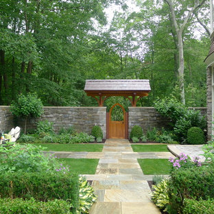 Large traditional backyard formal garden in New York with natural stone pavers and a garden path.