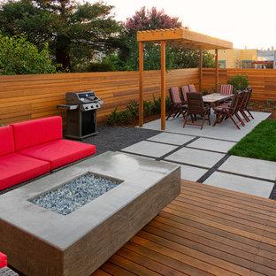 Идея дизайна: маленький солнечный, геометрический участок и сад на заднем дворе в стиле модернизм с местом для костра, хорошей освещенностью и настилом