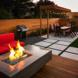 Inspiration for a small modern full sun backyard formal garden in San Francisco with a fire pit and decking.