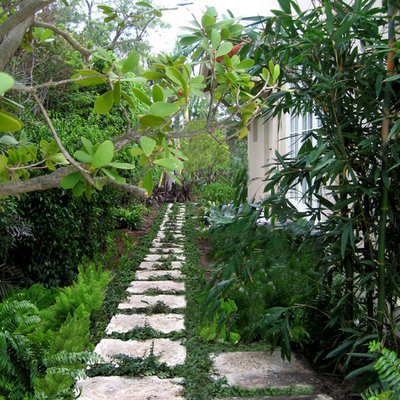 Photo of a mid-sized traditional side yard stone landscaping in Miami.