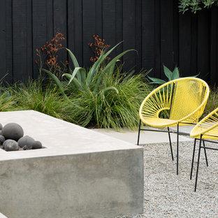 Immagine di un giardino design dietro casa con un focolare e pavimentazioni in cemento