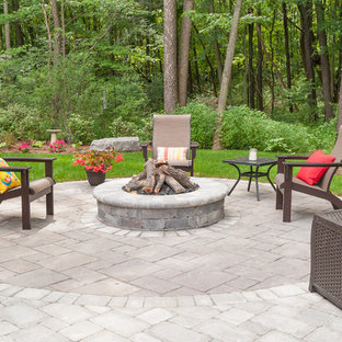 Inspiration for a large eclectic drought-tolerant and partial sun backyard brick landscaping in Grand Rapids with a fire pit for summer.