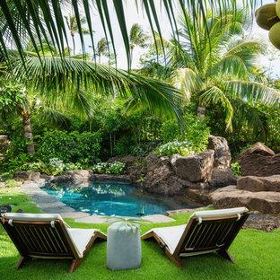 Aménagement d'un grand jardin arrière exotique l'été avec une exposition partiellement ombragée et des pavés en pierre naturelle.