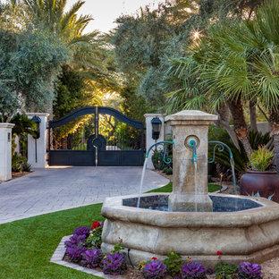 Diseño de acceso privado mediterráneo, en patio delantero, con fuente y adoquines de hormigón