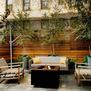 This is an example of a modern shade backyard stone landscaping in New York with a fire pit.