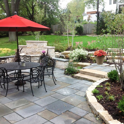 This is an example of a mid-sized traditional full sun backyard stone landscaping with a fire pit.