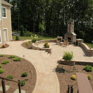 Idée de décoration pour un très grand jardin arrière tradition avec une cheminée, une exposition ensoleillée et des pavés en béton.