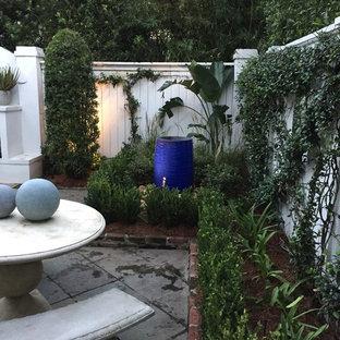 Mittelgroßer Klassischer Garten hinter dem Haus mit Kamin und Betonplatten in New Orleans