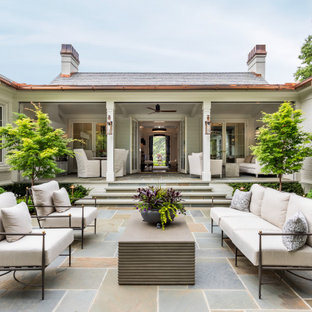 Photo of a large transitional courtyard partial sun formal garden in Other with a water feature and natural stone pavers.