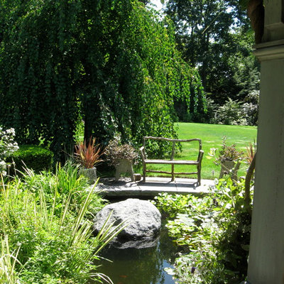 Design ideas for a large traditional partial sun backyard stone landscaping in Boston for summer.