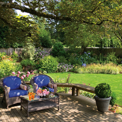 This is an example of a large traditional partial sun backyard formal garden in Portland with decking.