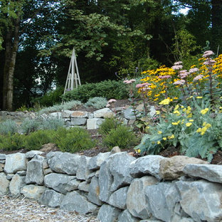 This is an example of a large traditional sloped partial sun formal garden in Portland with mulch and a retaining wall.