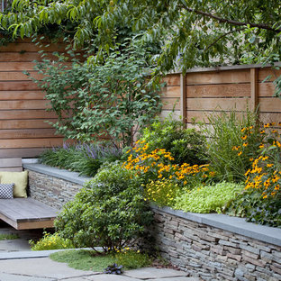 This is an example of a mid-sized modern partial sun backyard stone retaining wall landscape in New York for summer.