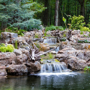 This is an example of a large rustic backyard stone pond in New York.