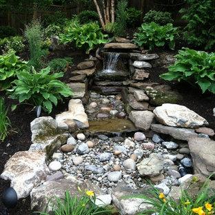 Exemple d'un jardin arrière asiatique de taille moyenne et au printemps avec une exposition partiellement ombragée, des pavés en pierre naturelle et une cascade.