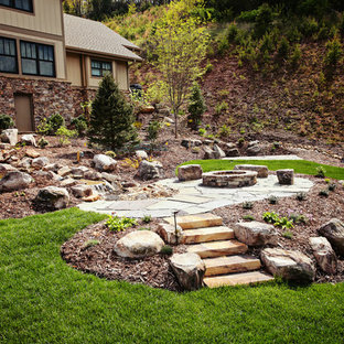 This is an example of a mid-sized traditional full sun backyard stone landscaping in Charlotte with a fire pit.