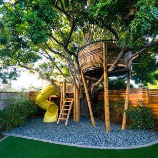 Modelo de jardín contemporáneo, grande, en patio trasero, con parque infantil y gravilla