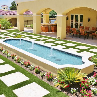 This is an example of a mid-sized mediterranean full sun backyard concrete paver water fountain landscape in Phoenix.
