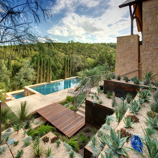 Photo of a large sloped xeriscape full sun garden in Austin with concrete paving and a desert look.