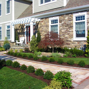 This is an example of a mid-sized traditional front yard full sun formal garden in New York with a garden path and natural stone pavers.