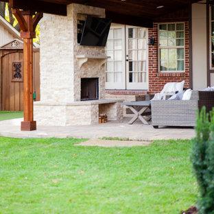 Halbschattiger Klassischer Garten hinter dem Haus mit Kamin, Natursteinplatten und Holzzaun in Dallas