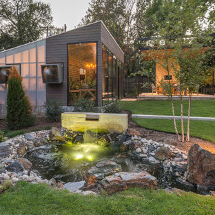 Photo of a large contemporary partial sun backyard water fountain landscape in Dallas.