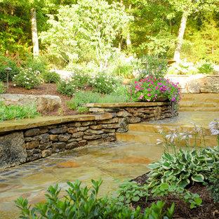Réalisation d'un jardin arrière nordique l'été avec une exposition ombragée et des pavés en pierre naturelle.