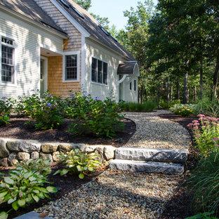 Idée de décoration pour un grand jardin avant tradition avec du gravier, un mur de soutènement et une exposition partiellement ombragée.