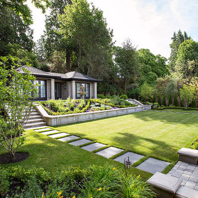 Photo of a large traditional partial sun hillside brick formal garden in Vancouver.