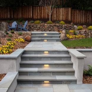 Immagine di un grande giardino minimal esposto a mezz'ombra dietro casa in inverno con pavimentazioni in pietra naturale e un muro di contenimento
