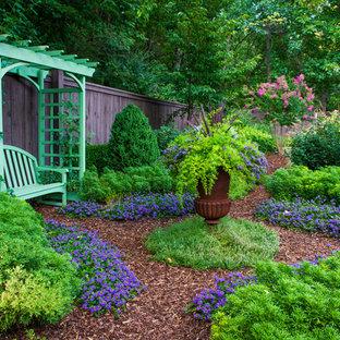 Cette image montre un jardin à la française arrière chalet avec un paillis.