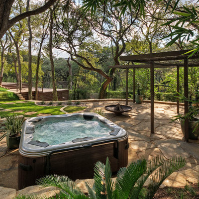 Design ideas for a large traditional shade hillside stone landscaping in Austin for summer.