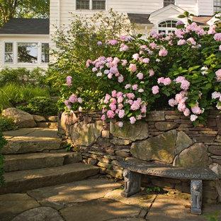 Cette image montre un jardin traditionnel l'été avec une pente, une colline ou un talus et des pavés en pierre naturelle.